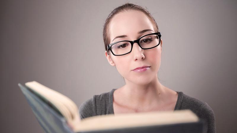 una mujer con gafas de pasta que está leyendo un libro