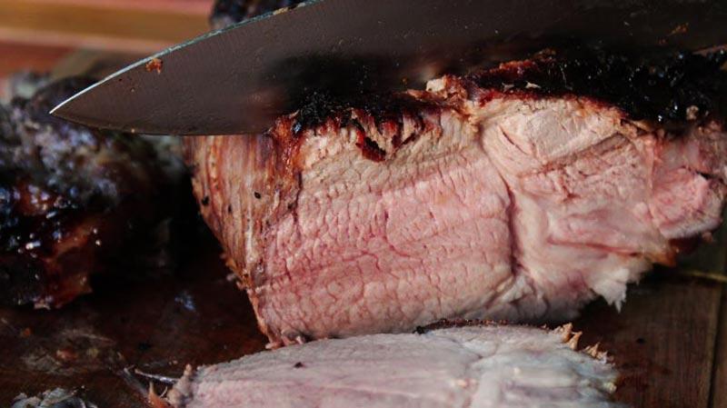 un cuchillo cortando un trozo de carne asada