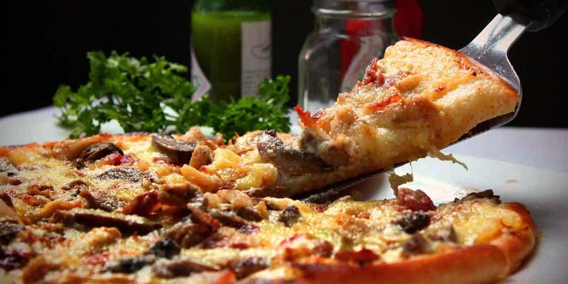 pizza con una espátula cogiendo una porción