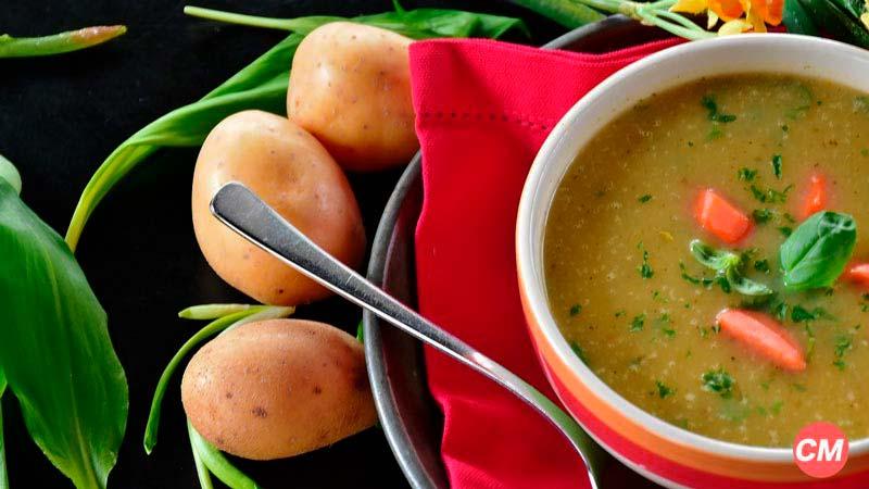 bol con sopa que tiene trozos de zanahoria y que tiene tres patatas en la izquierda