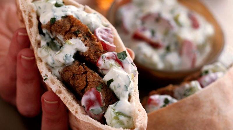 una mano sosteniendo un pan de pita relleno de carne y salsa con otros dos bocadillos al fondo desenfados