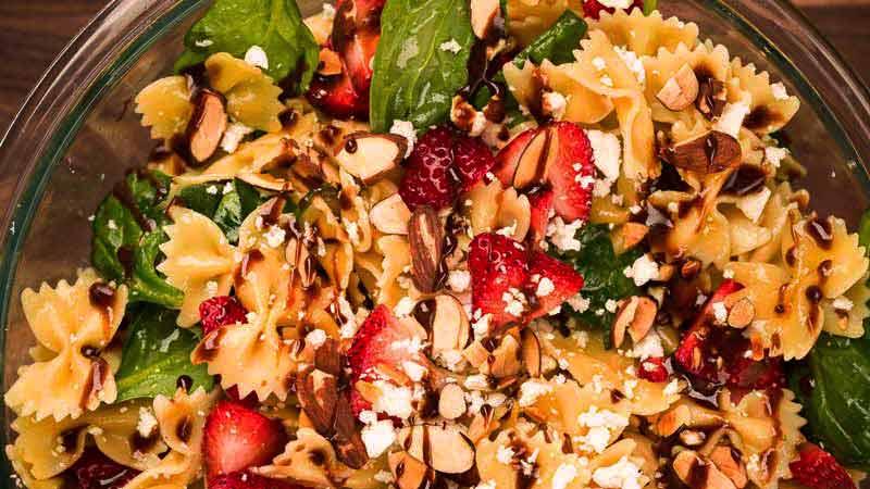 plato de cristal con pasta, hojas, fresas, queso y vinagre balsámico