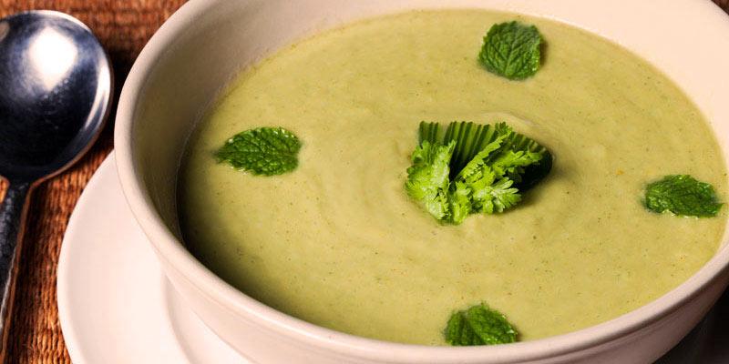 plato blanco con gazpacho dentro con hojas verdes en el centro y en extremos