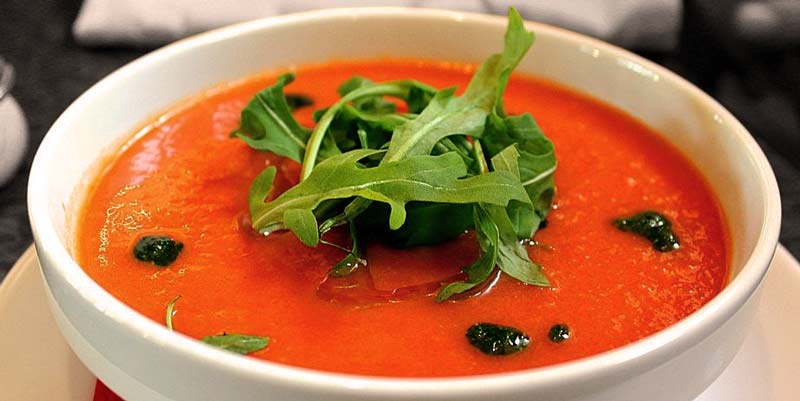 plato blanco hondo con gazpacho naranja y con hojas verdes en el centro