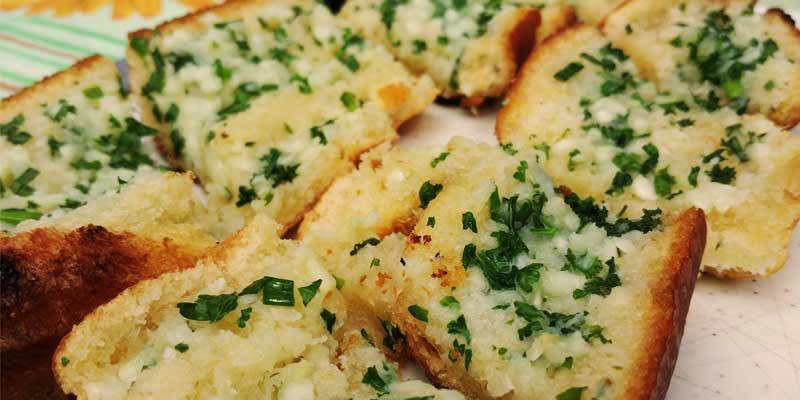 pan con ajo y perejil sobre una mesa con mantel a rayas