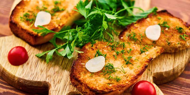 pan con ajo y perejil sobre una tabla de madera, la cual está sobre una mesa de madera