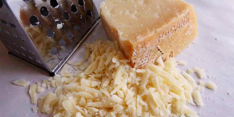 trozo de queso con más queso rallado al lado y con un rallador metálico