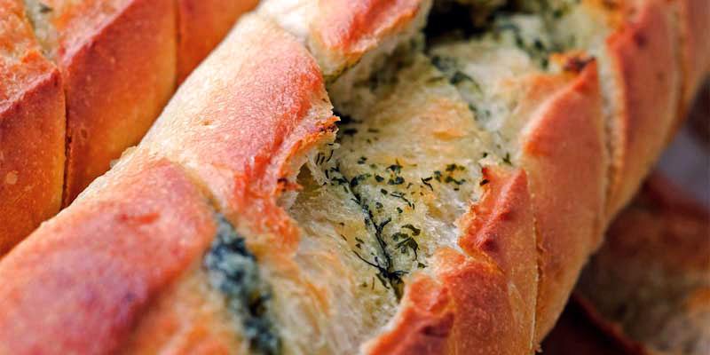 una barra de pan cortada en rebanadas con perejil