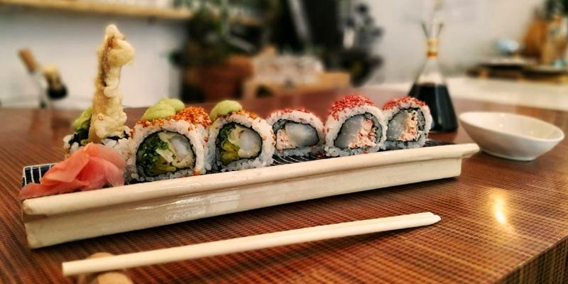 bandeja de sushi en una mesa marrón y con palillos chinos blanco delante