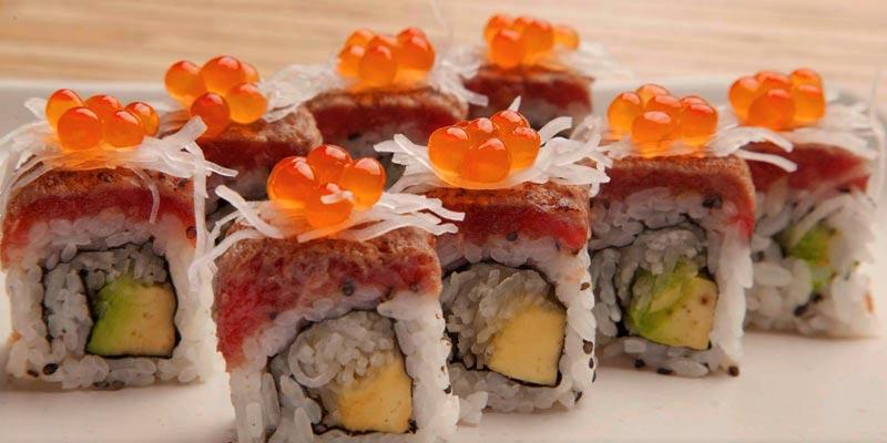 sushi en fila sobre una bandeja blanca