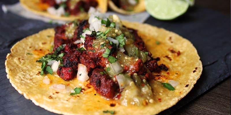 taco con carne y cebolla sobre un mantel azul y con más tacos al fondo