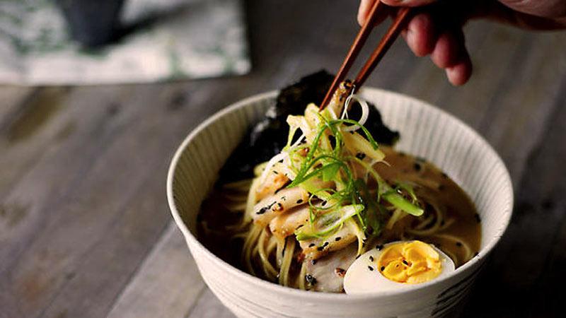 una mano sosteniendo palillos chinos marrones que cogen parte de comida de un plato hondo blanco