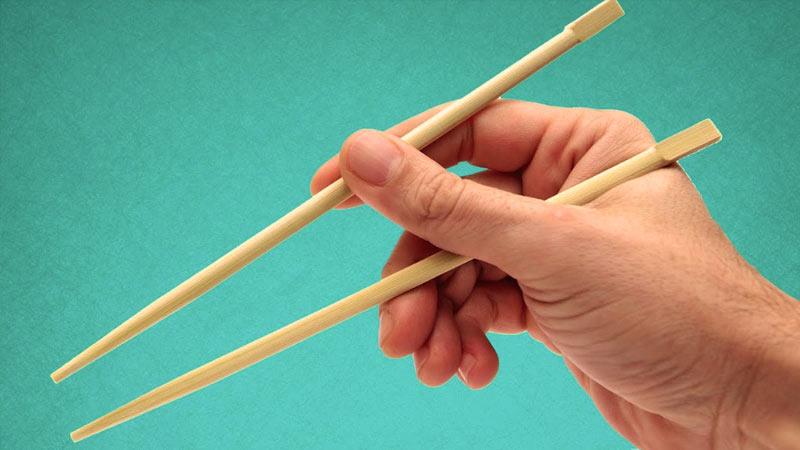 una mano sosteniendo dos palillos chinos sobre un fondo color azul
