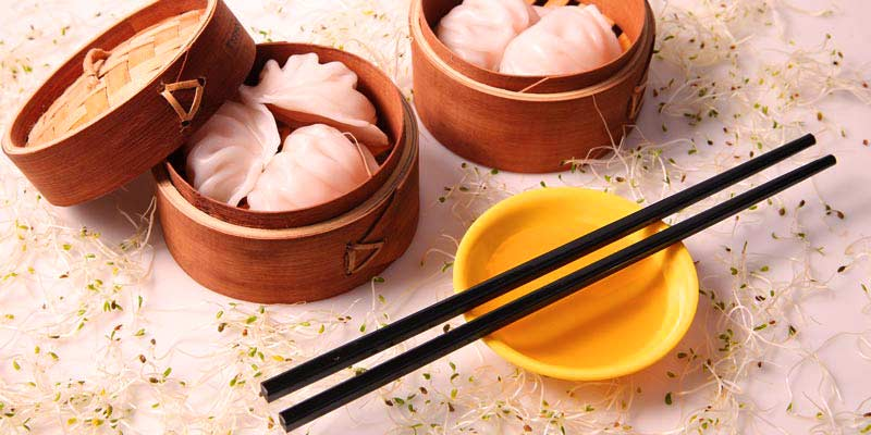 cajas redondas con empanadillas asiáticas y con palillos chinos negros sobre un recipiente amarillo