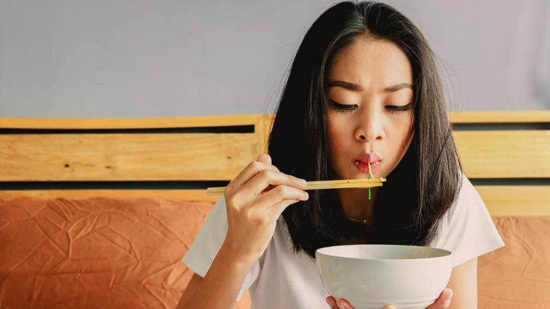 una mujer asiática que sostiene unos palillos chinos al comer y mientras sostiene también un bol blanco