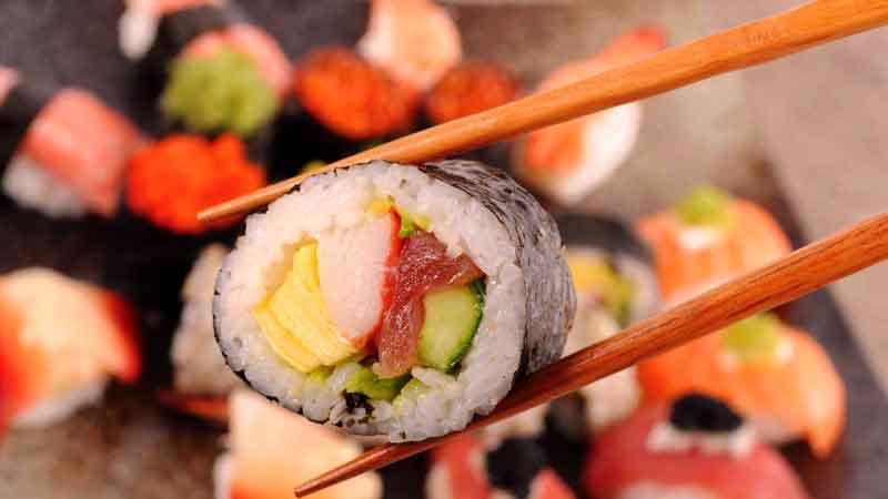 unos palillos chinos sosteniendo una pieza de sushi con mucho más en el fondo desenfocados