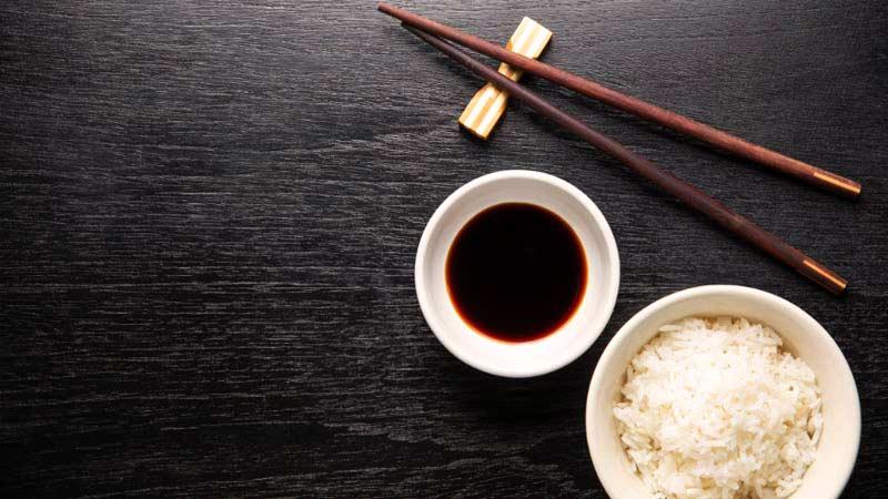 dos platos blancos, uno con salsa de soja y otro con arroz, al lado de unos palillos chinos marrones y encima de una mesa de madera negra