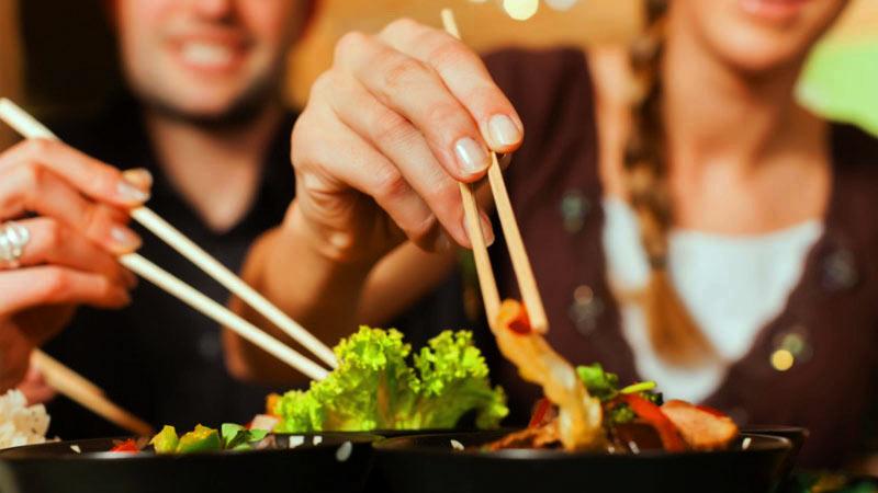 dos personas a las cuales no se les ve la cara y que sostienen unos palillos chinos para coger la comida de unos platos negros