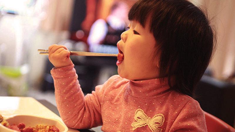 una niña china que se lleva unos palillos chinos a la boca y que tiene un jersey rosa con un lazo blanco