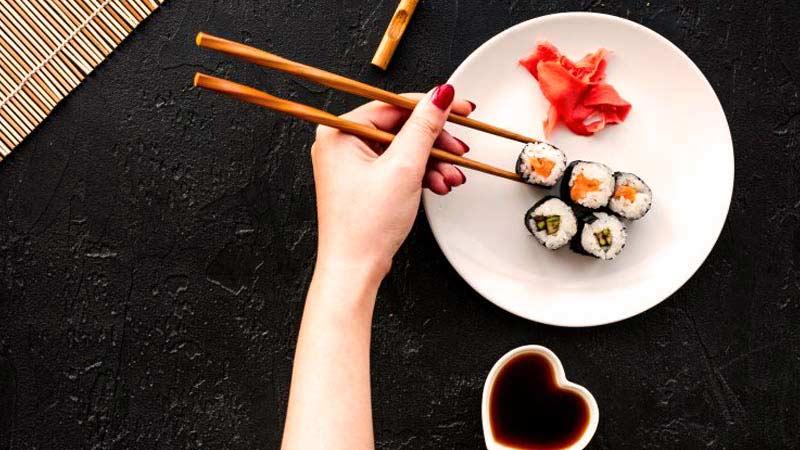 una mano con las uñas pintadas que sostiene unos palillos chinos para coger una pieza de sushi de las cinco que hay en un plato blanco