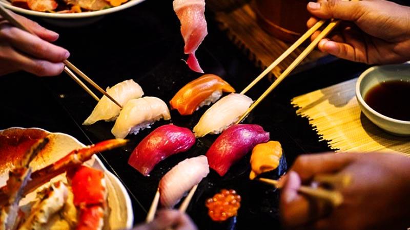 varias manos sosteniendo palillos chinos para coger trozos de sushi que hay en el centro en una placa negra