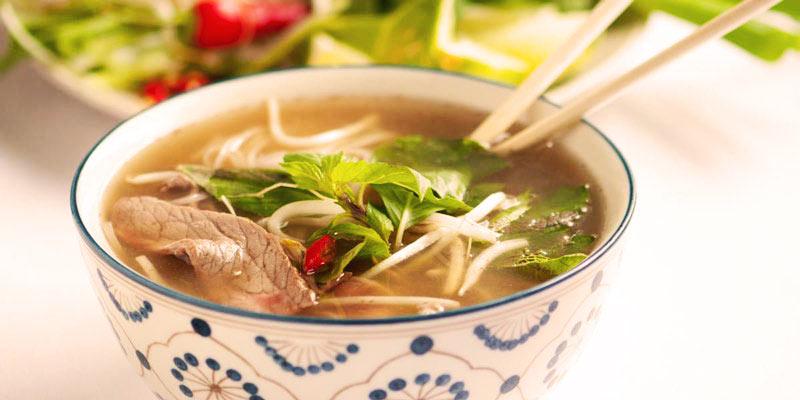 sopa en un bol blanco con decoraciones azules y con una ensalada al fondo