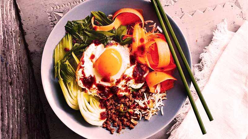comida asiática, bibimbap en un bol azul con palillos verdes.