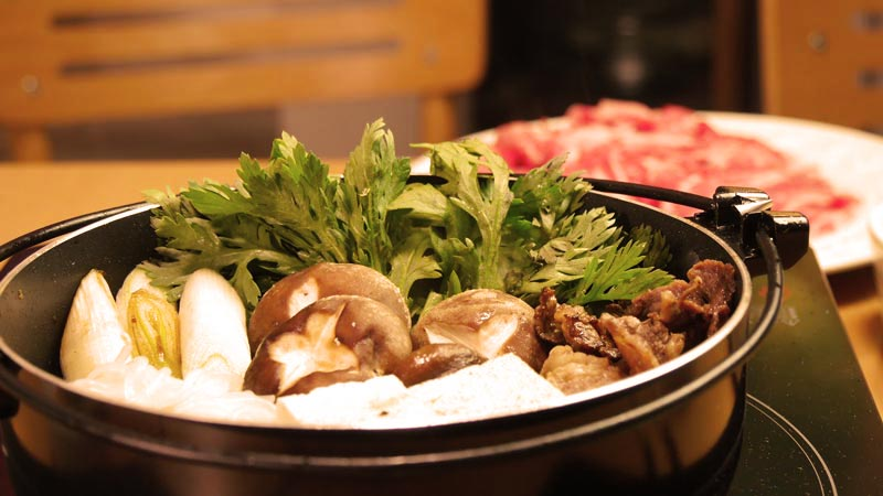 comida asiática. olla con sukiyaki y carne en un plato al fondo