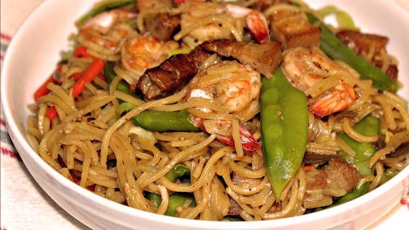 comida asiática, fideos con gambas, carne y zanahoria en un bol blanco