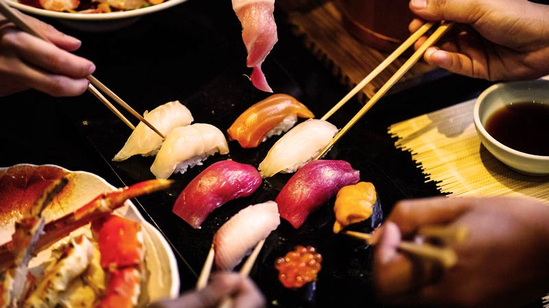 Comensales con palillos cogiendo sushi
