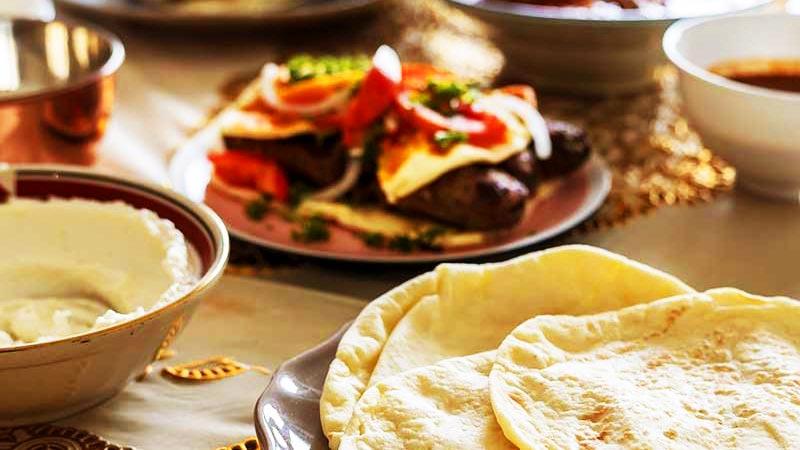 una mesa con un mantel marrón con varios platos llenos de comida