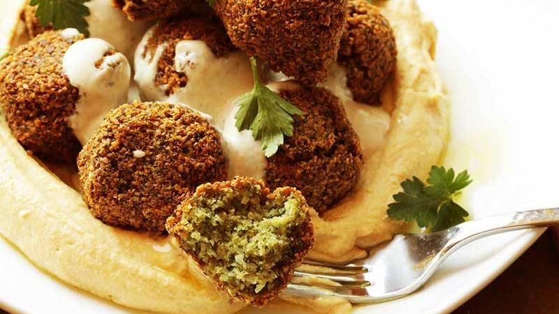 faláfel encima de hummus en un plato blanco