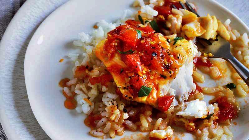 bacalao con arroz y salsa de tomate y verduras sobre un plato doble blanco