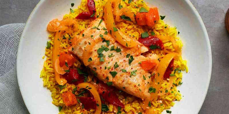 bacalao con arroz amarillo y verduras en un plato blanco sobre un mantel gris
