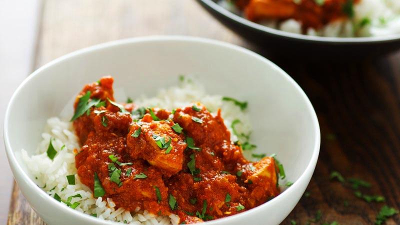 pollo troceado con tomate y curry encima de arroz en un bol blanco
