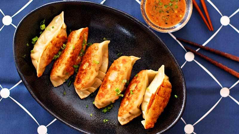 empanadillas tostadas en un plato ovalado negro sobre un mantel azul y con palillos chinos al lado