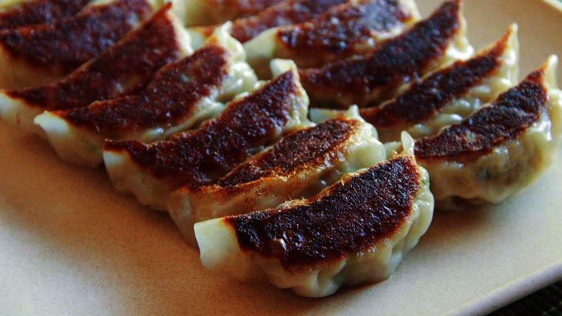 muchas empanadillas tostadas en un plato blanco