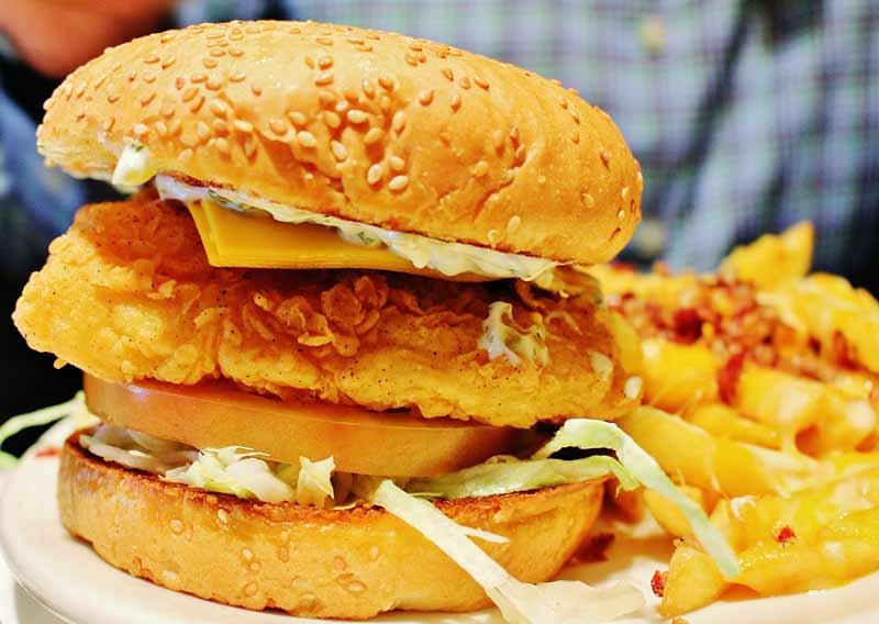 hamburguesa de pescado en plato con chips de patatas