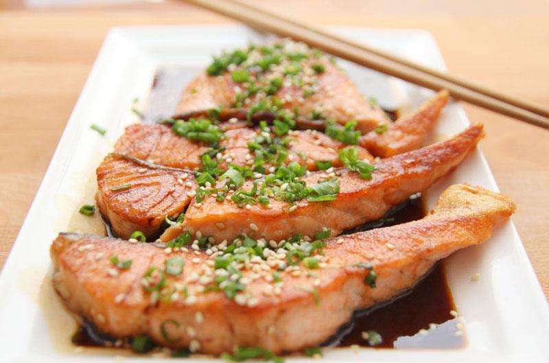filetes de salmon marinados en salsa de soja con dos palillos chinos
