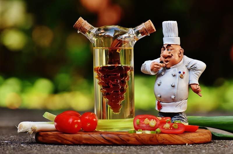 Vinagre en una botella con un muñeco de cocinero al lado sobre una mesa-Tipos de vinagres